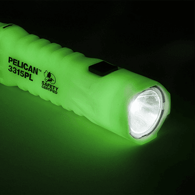 Side angled view of the 3315PL photoluminescent torch glowing against a black background
