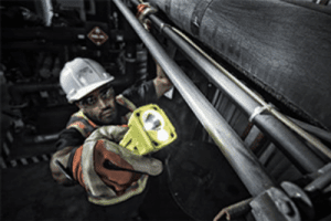 Hand held IECEx approved 3415 flashlight being used in an industrial application.